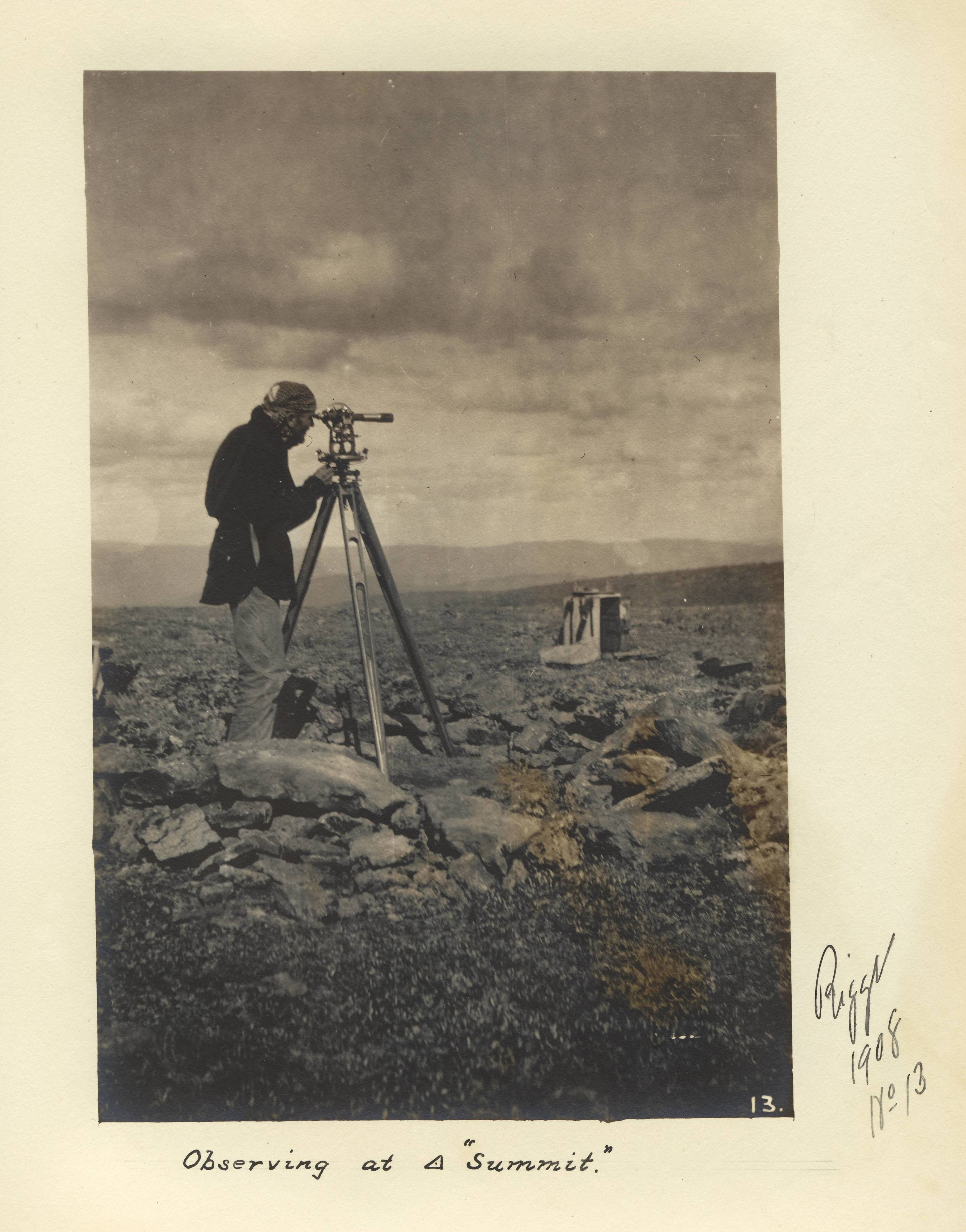 photo of a man looking through a scope on rocky terrain