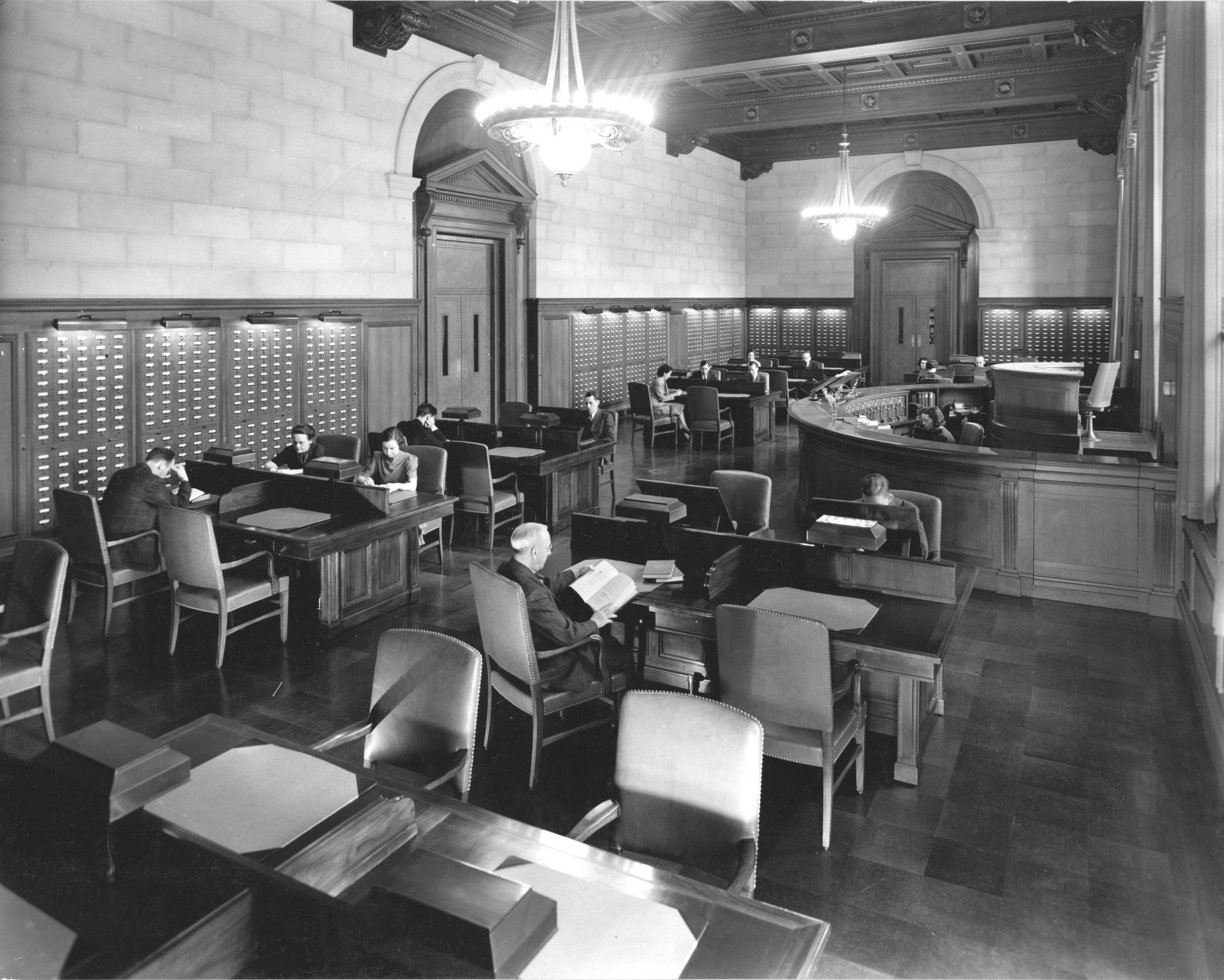 men and women sitting at desks in the central search room