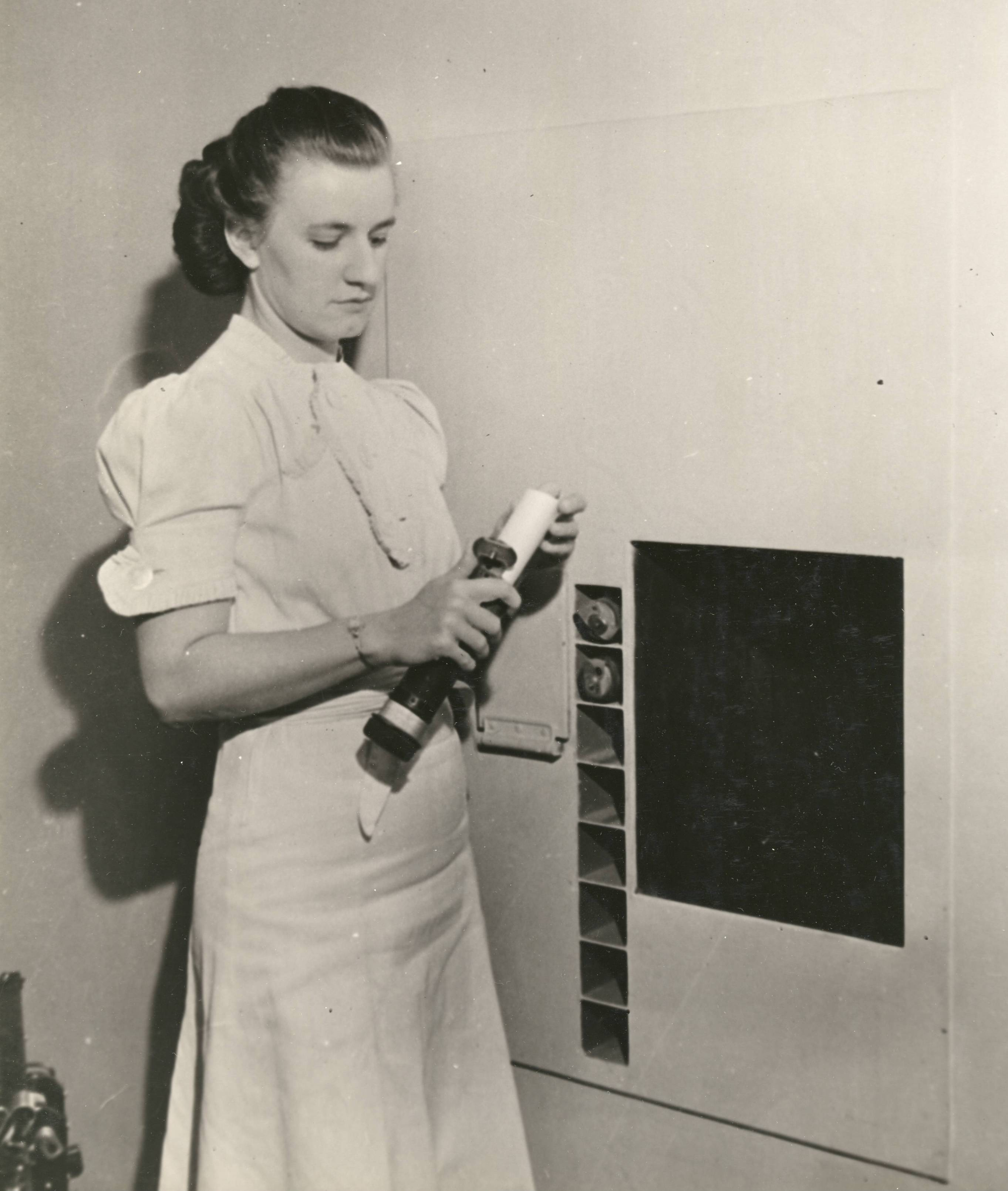 64-NA-340 Edith Houbert Retrieves Request from Pneumatic Tube, 1940 - cropped