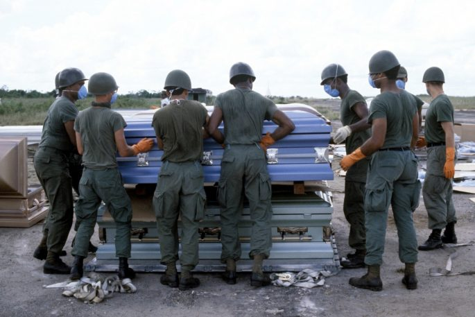 Image of US Military personnel stack coffins containing the remains of the victims of the Jonestown Tragedy for transport to Dover Air Force Base, Delaware (NAID 6413436)