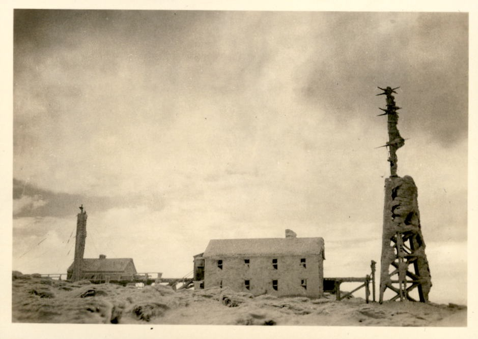 Image of radio tower and adjacent buildings covered with snow.