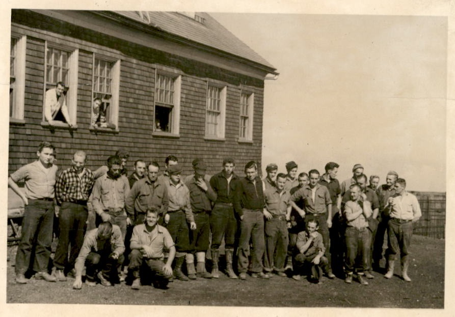 Image of men posing for the camera outside a building.