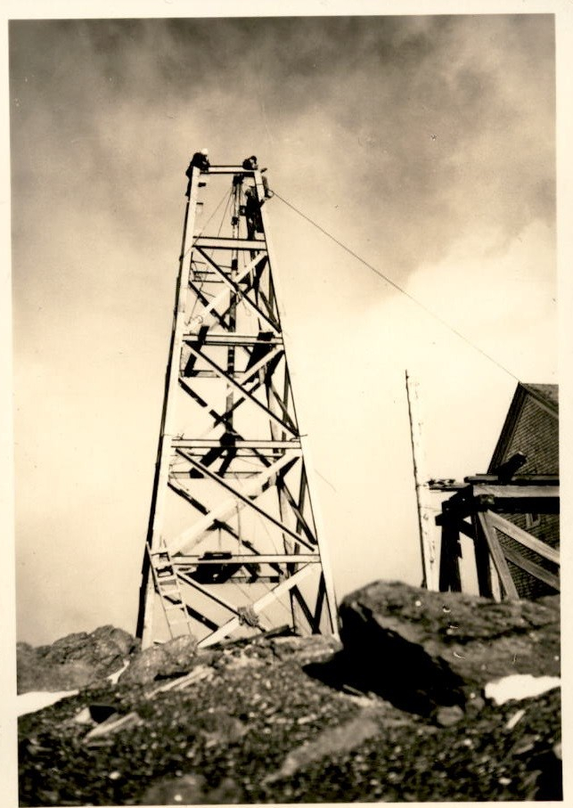 Image of a tall antenna tower with workers on top of it.