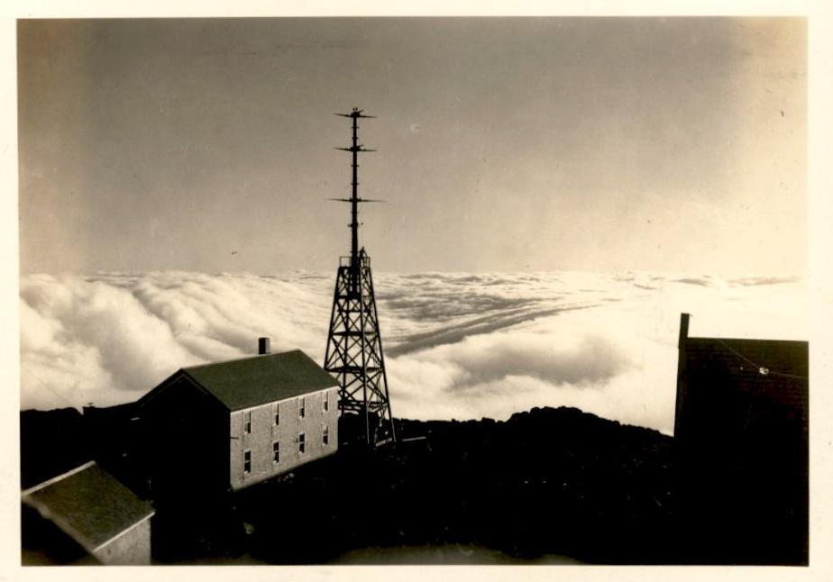 Image of tower and other buildings with clouds in the background