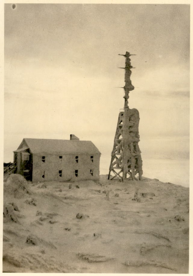 Image of radio tower and building adjacent to it covered with snow.