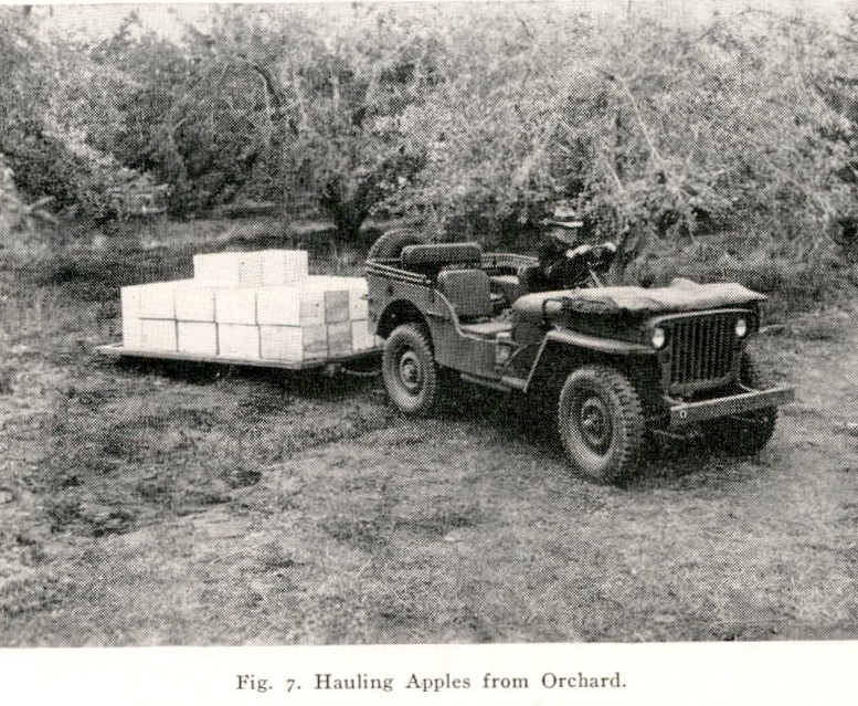 picture of a jeep towing a flatbed stacked with apples