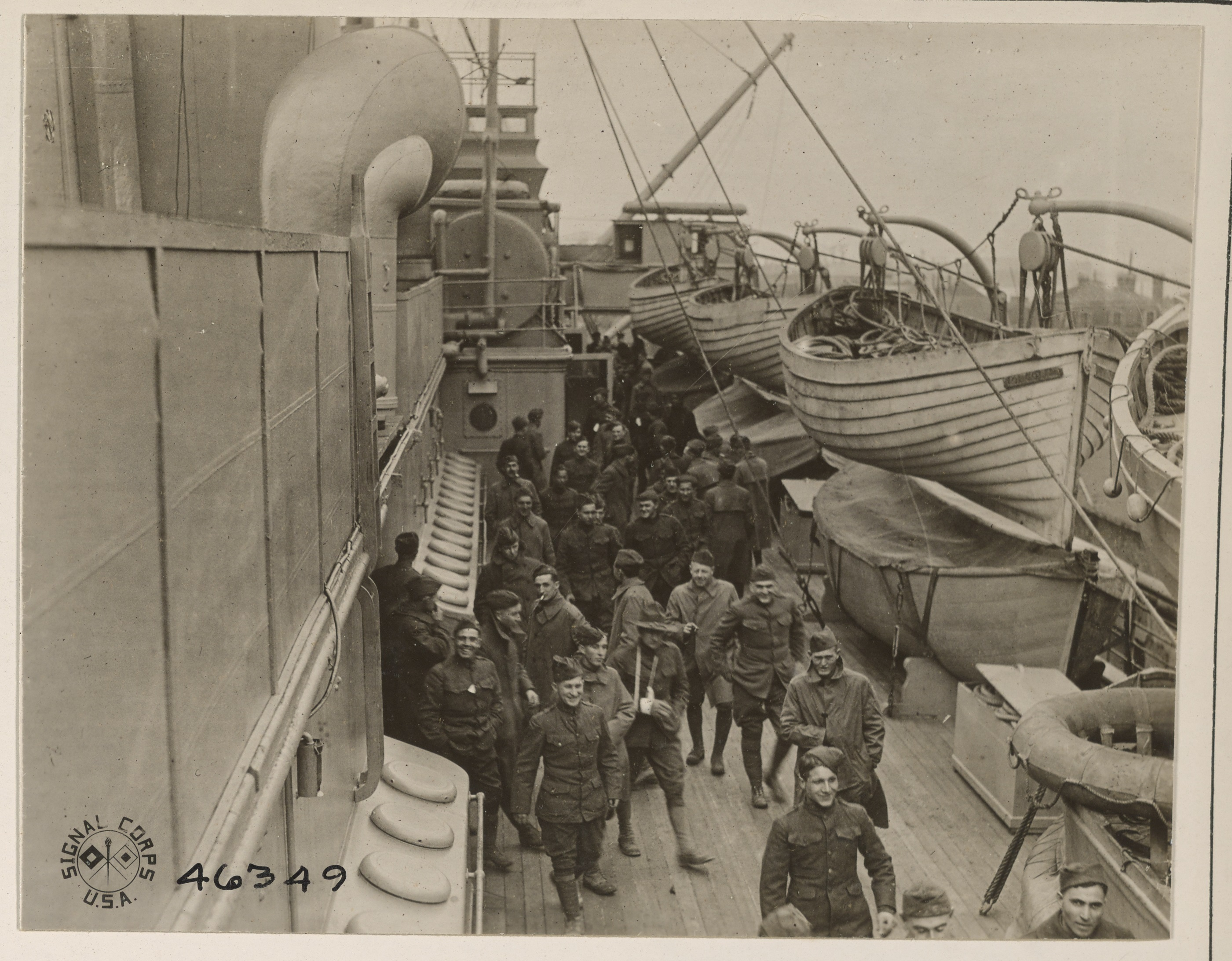 black and white photo of soldiers standing on a ship's dock