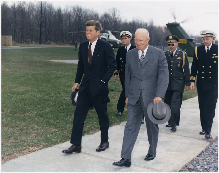 Presidents Kennedy & Eisenhower walking side by side and smiling