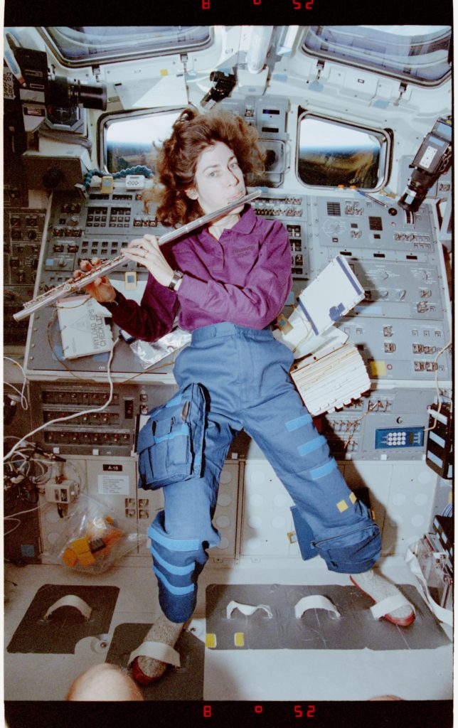 Ochoa playing flute. Feet are strapped down to hold her in place in 0 gravity